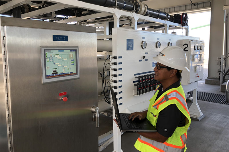 Trimax technician viewing computer and operator interface at a plant