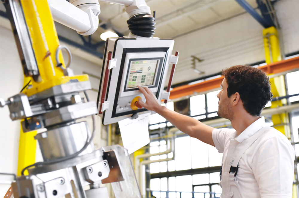 factory worker inputting data on screen