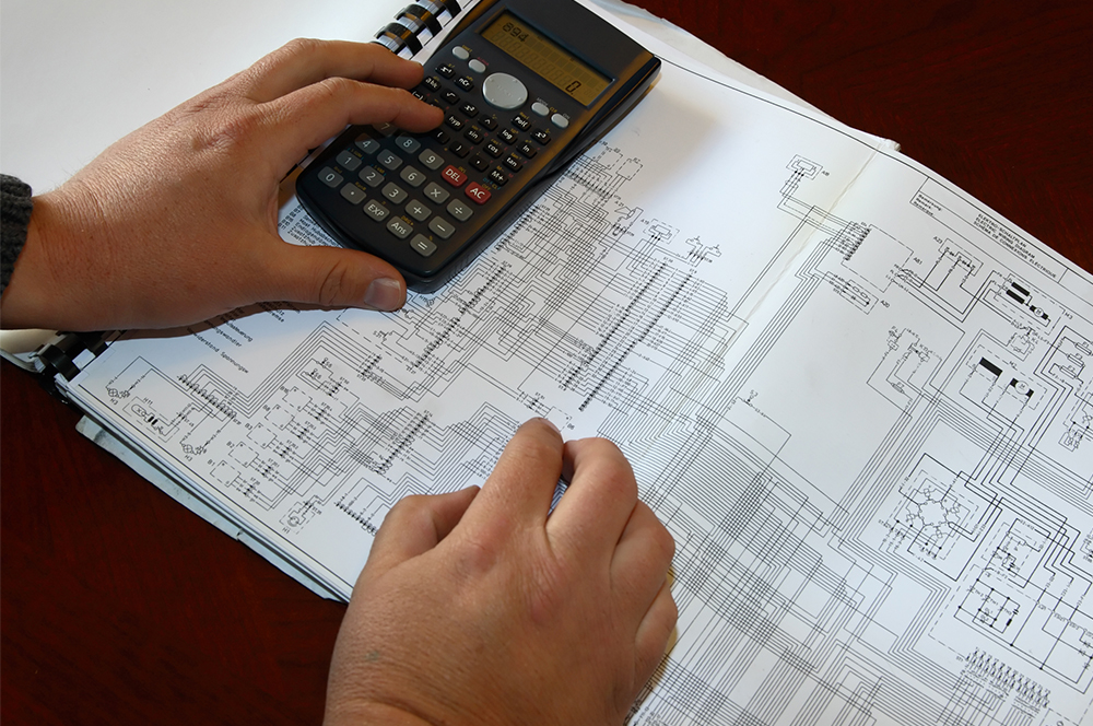 Person reviewing electrical drawings with calculator