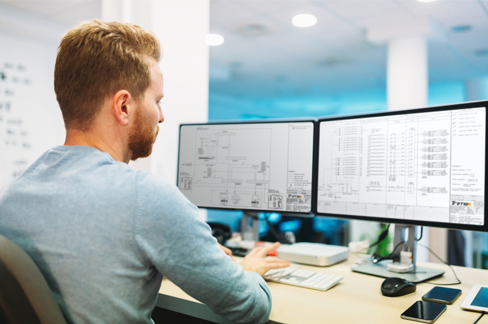 engineer reviewing electrical drawings on computer screens